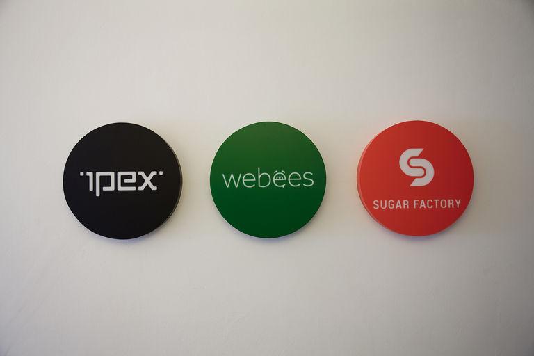 loga firem naproti vstupním dveřím – kanceláře IPEX praha | Horalík Atelier